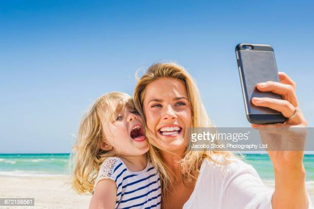 Caucasian mother and daughter posing for cell phone selfie at beach