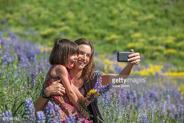 Caucasian mother and daughter posing for cell phone selfie on hillside with wildflowers