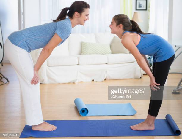 Caucasian mother and daughter practicing yoga in living room