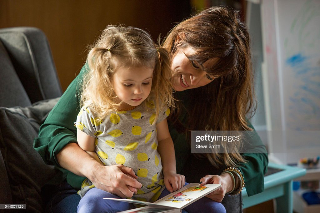 Caucasian mother and daughter reading book on sofa : Stock Photo