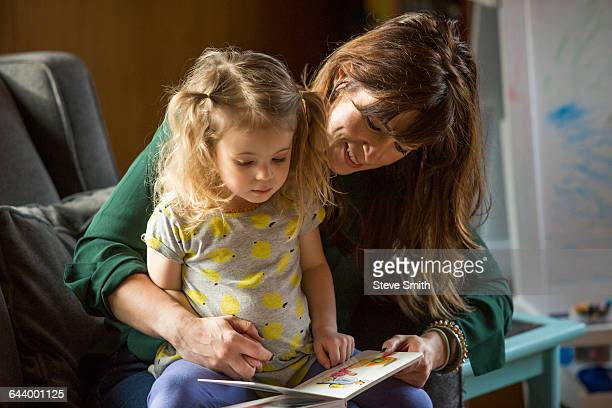 Caucasian mother and daughter reading book on sofa