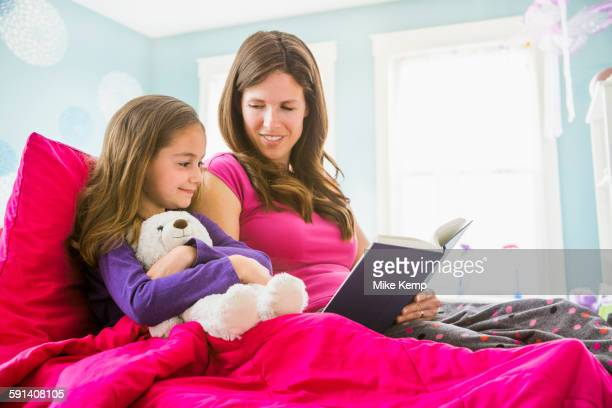 Caucasian mother and daughter reading in bed