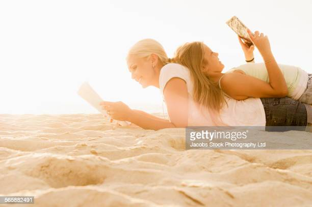 Caucasian mother and daughter reading on beach