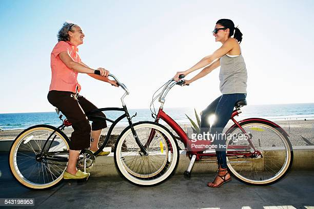 Caucasian mother and daughter riding bicycles near beach