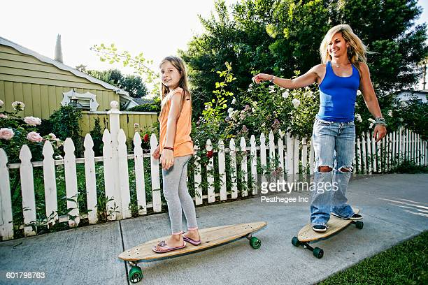 Caucasian mother and daughter riding skateboards on sidewalk