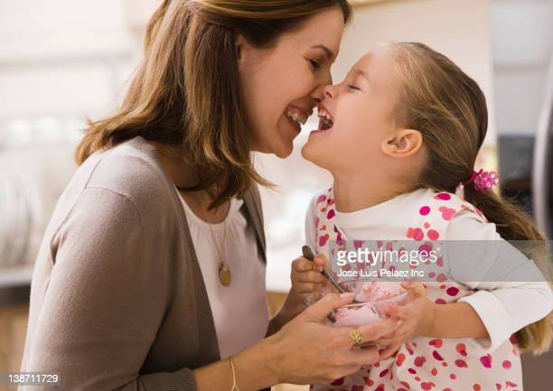 Caucasian mother and daughter rubbing noses and eating ice cream