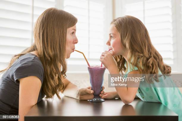 Caucasian mother and daughter sharing milkshake