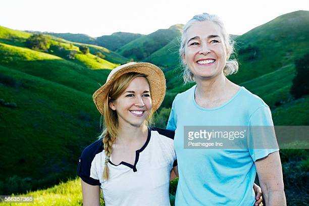 Caucasian mother and daughter smiling on rural hilltop