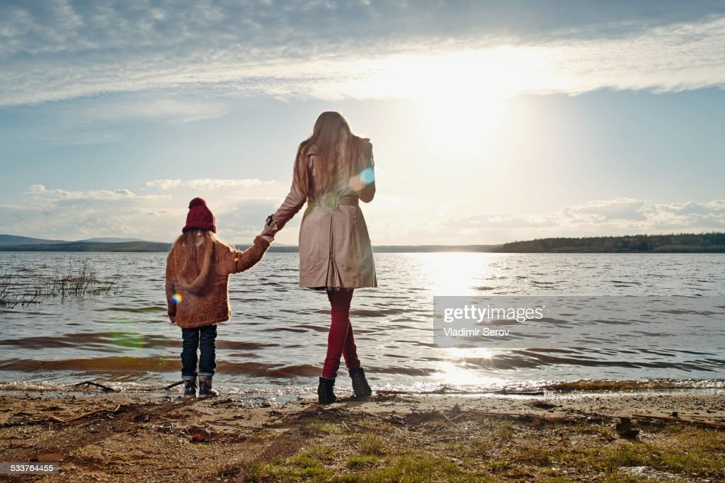 Caucasian mother and daughter standing on beach : Foto stock