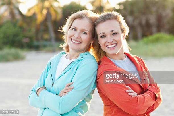 Caucasian mother and daughter standing on beach