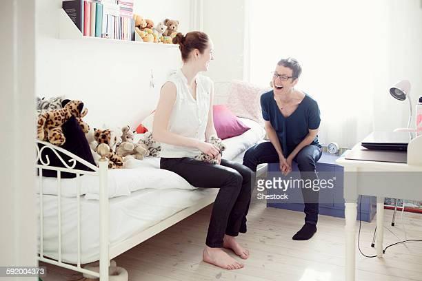Caucasian mother and daughter talking in bedroom
