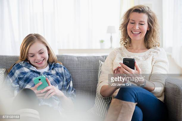 Caucasian mother and daughter using cell phones on sofa