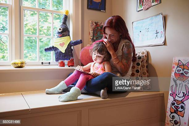 Caucasian mother and daughter using digital tablet
