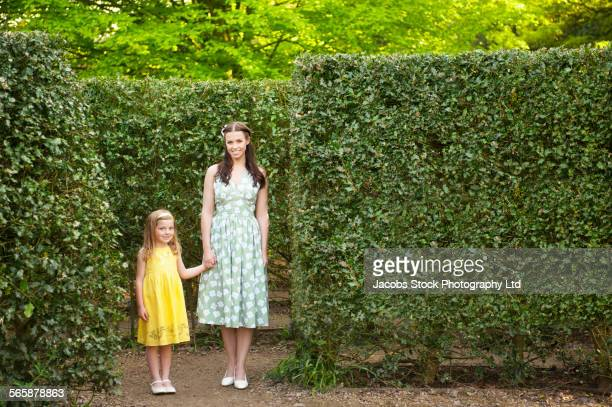 Caucasian mother and daughter walking in hedge maze