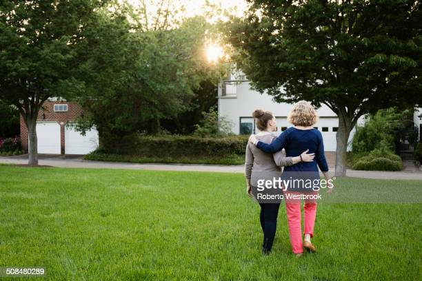 Caucasian mother and daughter walking in park