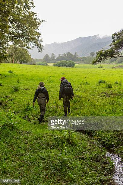 Caucasian mother and daughter walking in remote field