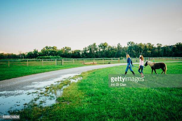 Caucasian mother and daughter walking miniature horse on farm