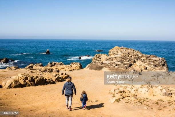 caucasian mother and daughter walking near ocean - seascape stock pictures, royalty-free photos & images