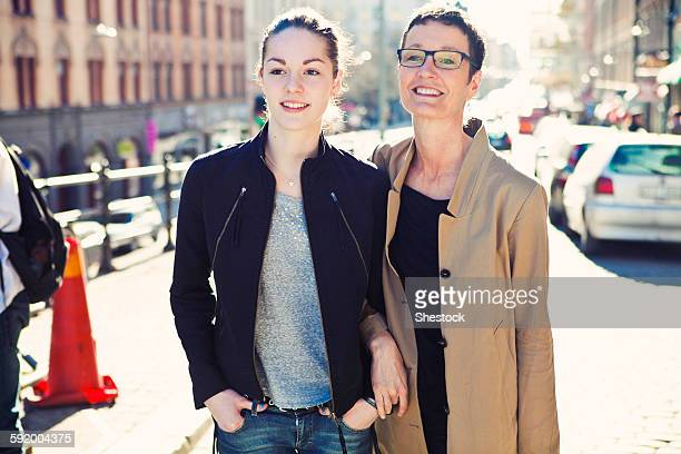 Caucasian mother and daughter walking on city sidewalk