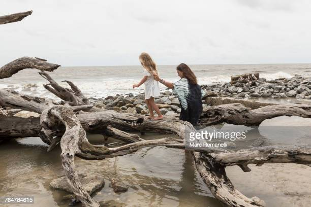 Caucasian mother and daughter walking on driftwood on beach