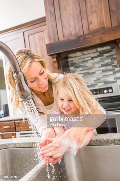 Caucasian mother and daughter washing hands in kitchen sink