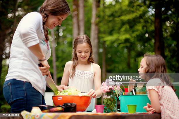 Caucasian mother and daughters cooking outdoors