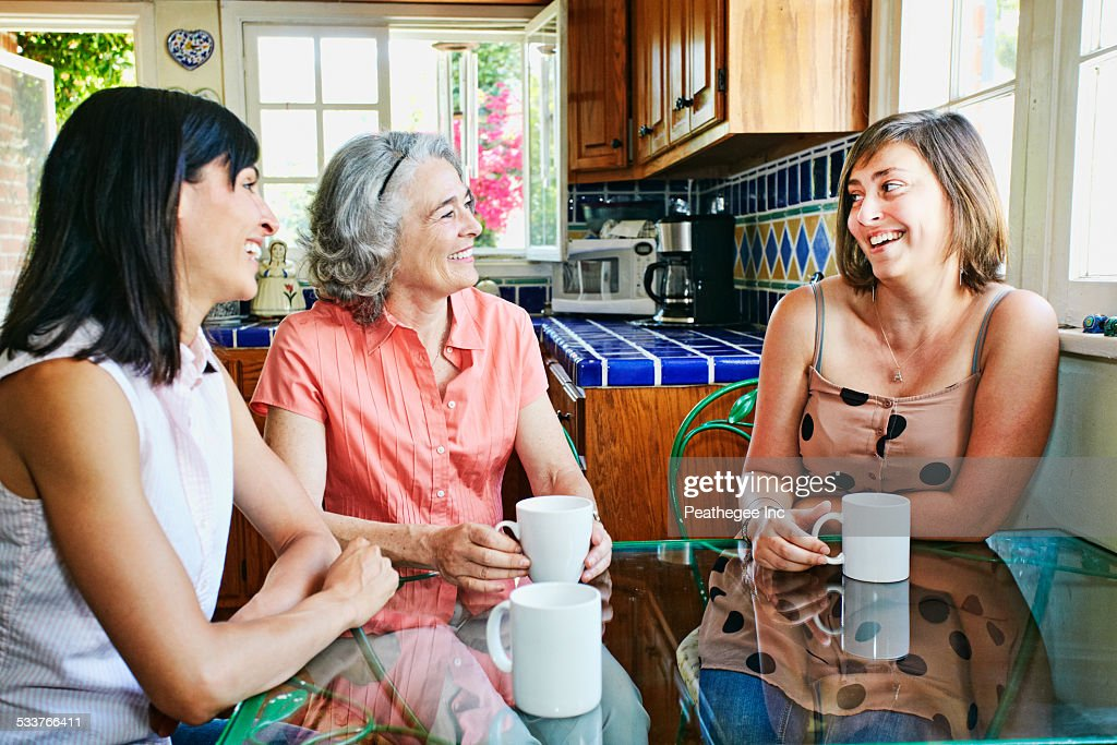 Caucasian mother and daughters drinking coffee in kitchen : Foto stock