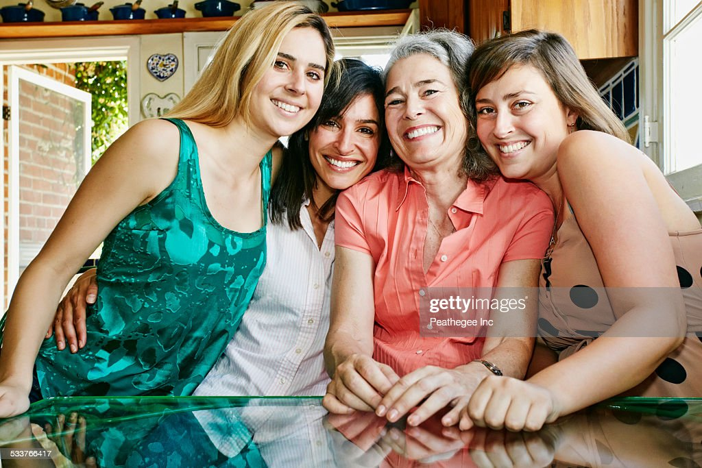 Caucasian mother and daughters hugging in kitchen : Foto stock