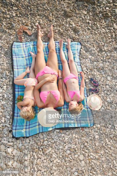 caucasian mother and daughters sunbathing on beach - girls sunbathing stock photos and pictures