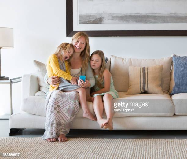 Caucasian mother and daughters using cell phone on sofa