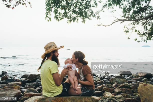 Caucasian mother and father holding baby daughter on rocky beach