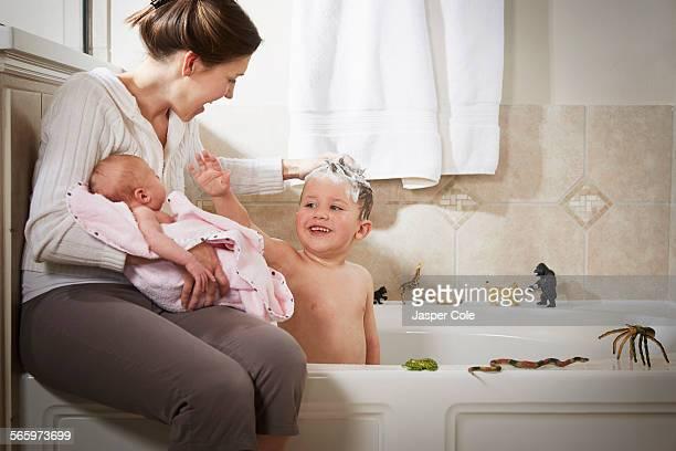 Caucasian mother and newborn washing son in bath