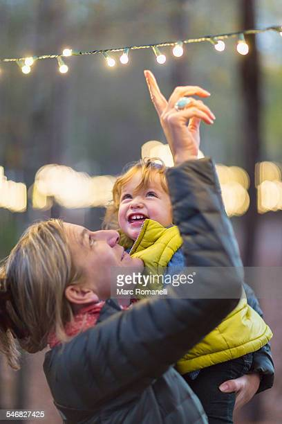 Caucasian mother and son admiring string lights