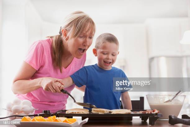 Caucasian mother and son cooking breakfast