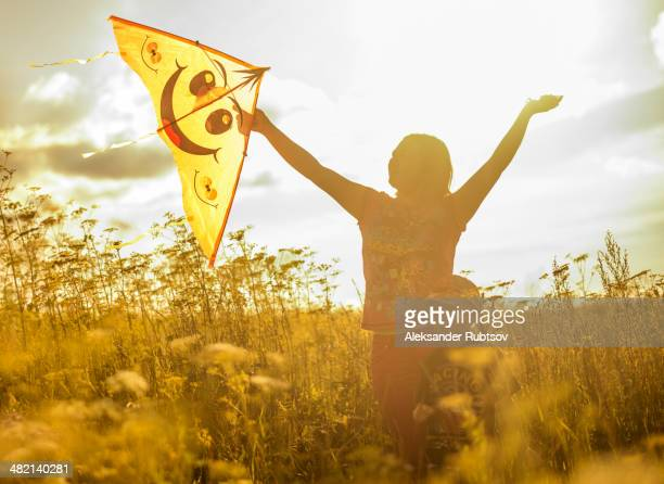 Caucasian mother and son flying kite in rural field