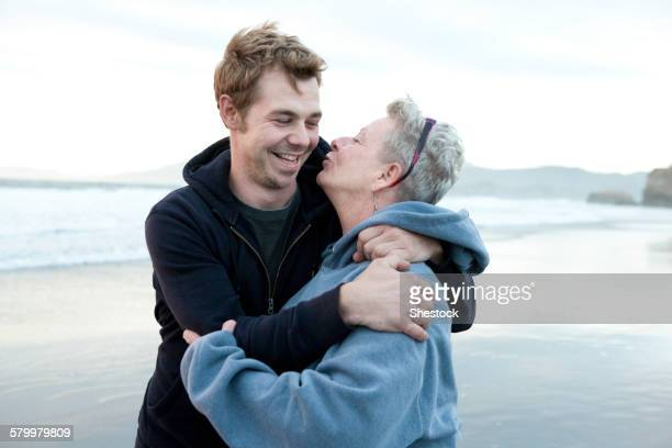 Caucasian mother and son hugging on beach