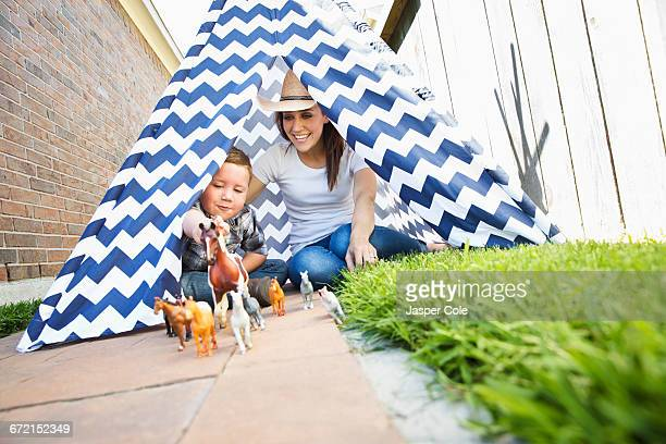Caucasian mother and son in teepee playing with toy horses