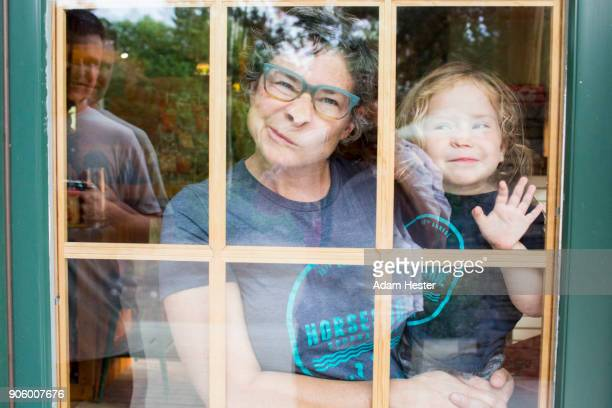 Caucasian mother and son making a face in door window