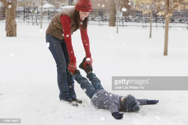 Caucasian mother and son playing in the snow