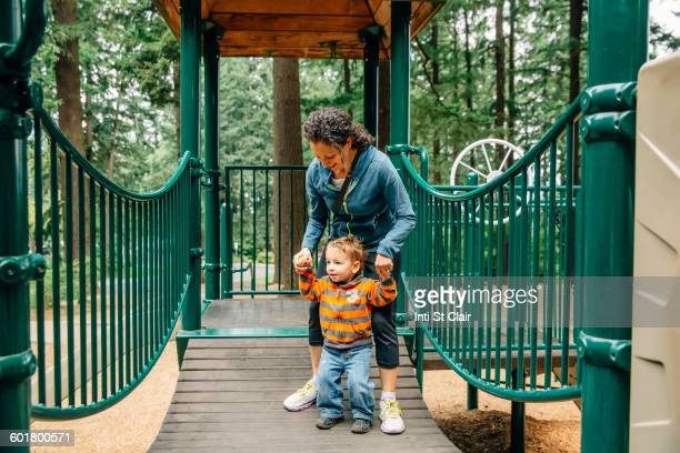 Caucasian mother and son playing on playground