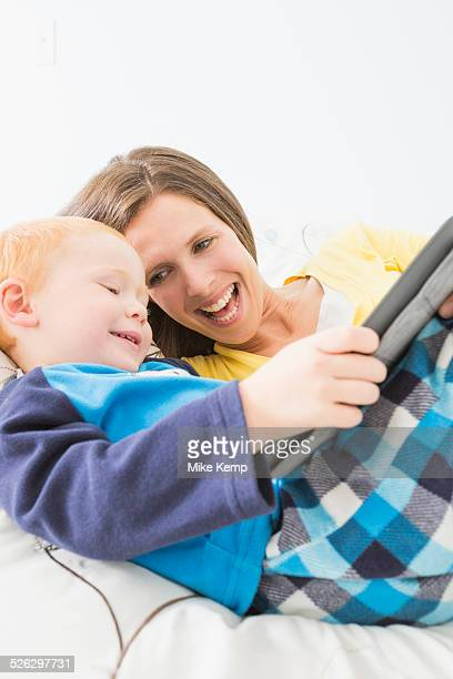 Caucasian mother and son using digital tablet in bed