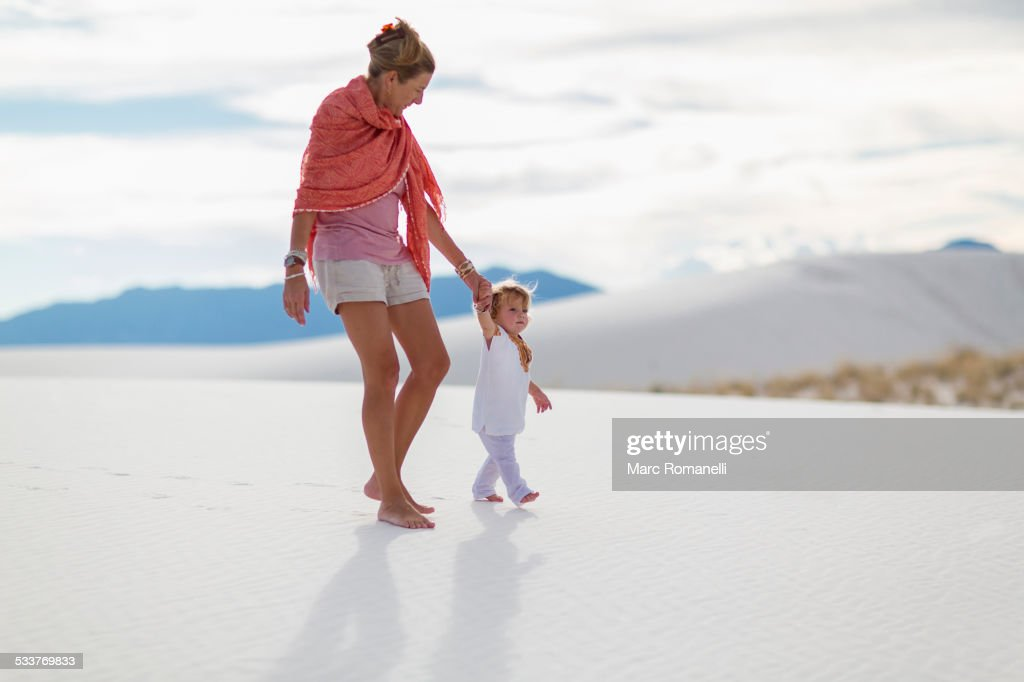 Caucasian mother and son walking on sand dune : Foto stock