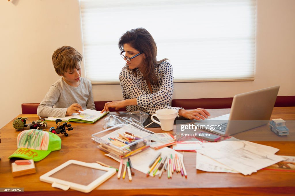 Caucasian mother and son working at table : Stock Photo