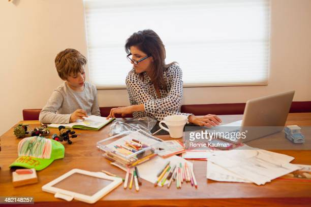 Caucasian mother and son working at table