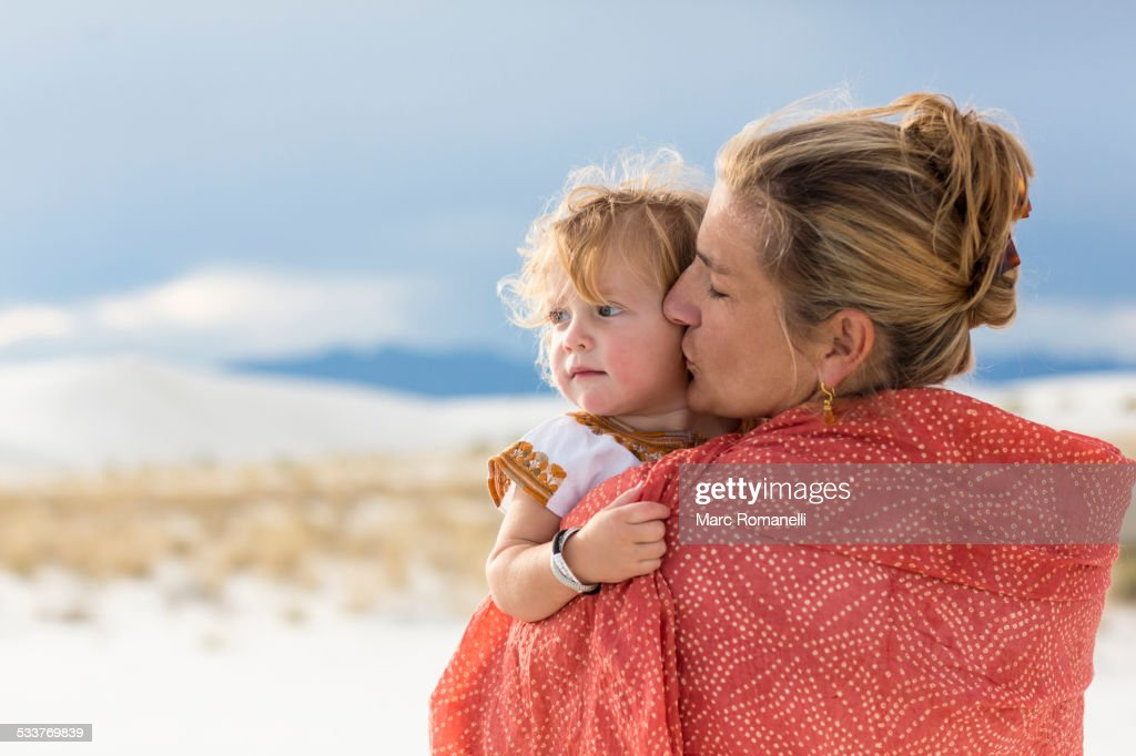 Caucasian mother and son wrapped in blanket on sand dune : Foto stock