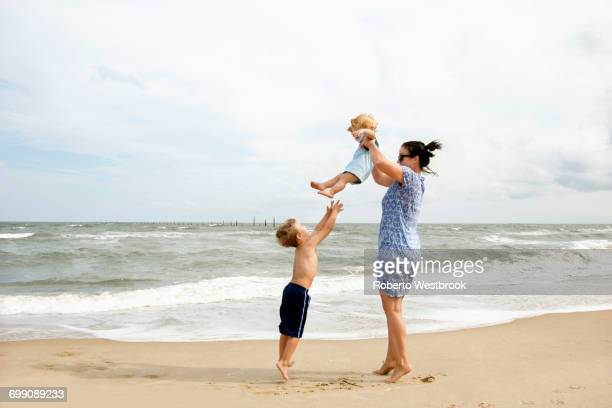 Caucasian mother and sons playing at beach