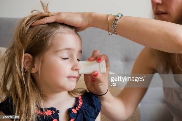 Caucasian mother applying sunscreen to face of daughter