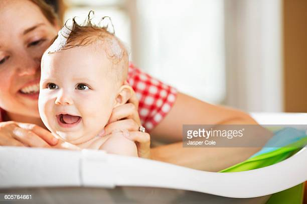 Caucasian mother bathing baby daughter