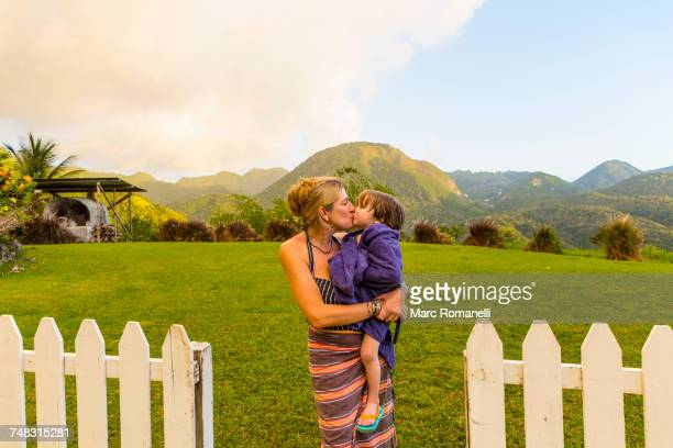 caucasian mother carrying and kissing son - wrapped in a towel stock pictures, royalty-free photos & images