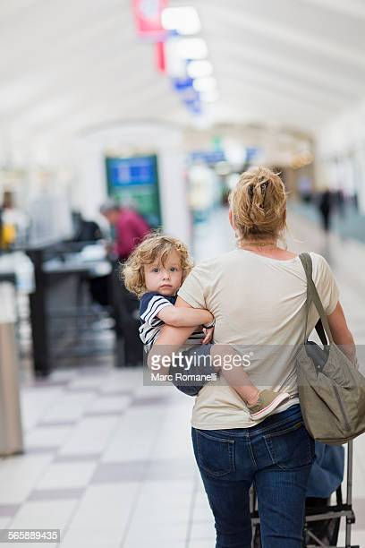 Caucasian mother carrying baby son in airport